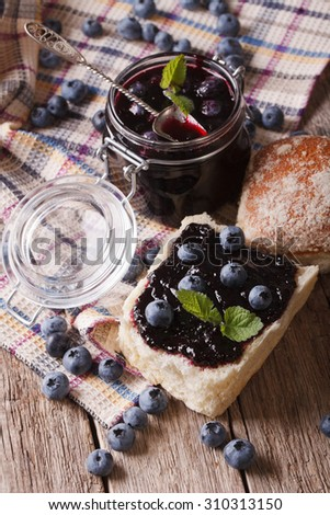 homemade blueberry jam and sweet bun close-up on the table. vertical - stock photo