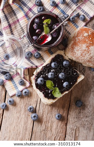 homemade blueberry jam and sweet bun close-up on the table. Vertical top view - stock photo