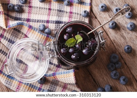 homemade blueberry jam in a glass jar on the table. horizontal top view - stock photo