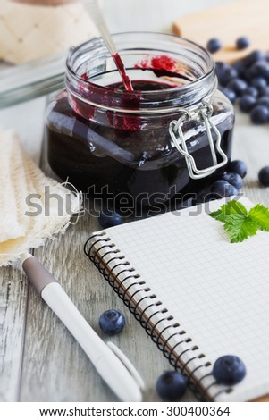homemade blueberry jam in a jar and fresh blueberries on a table. a place for an inscription. health and diet concept. selective focus - stock photo