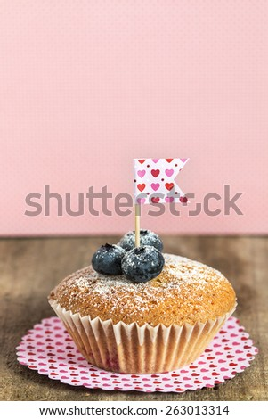 Homemade blueberry muffin with berries over vintage paper with hearts, macro with copyspace - stock photo