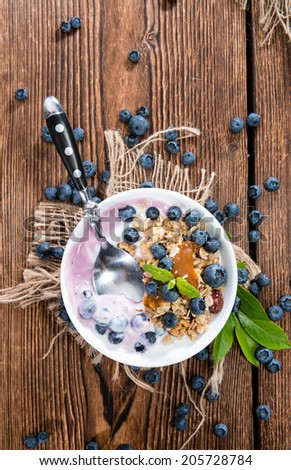 Homemade Blueberry Yogurt in a small bowl garnished with fresh fruits - stock photo