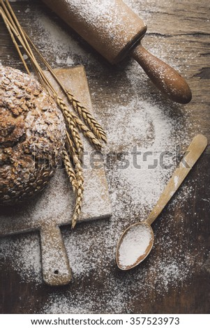 Homemade bread, flour, wheat ears and kitchen utensils on rustic table.