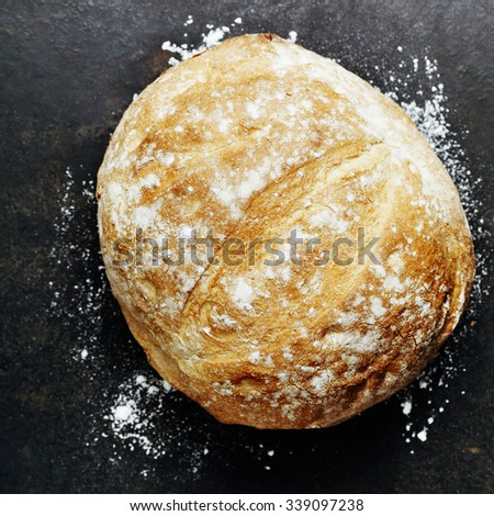 Homemade bread loaf on rustic dark background - stock photo