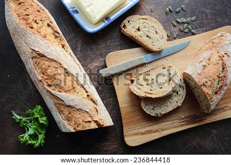 Homemade bread sliced on cutting board with butter - stock photo