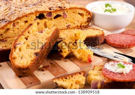 Homemade bread with salami. Selective focus on small bread pieces and knife with cream - stock photo