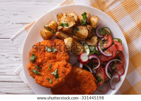 Homemade breaded German Weiner schnitzel with potatoes close-up. horizontal view from above - stock photo