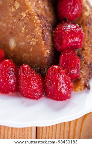 Homemade brown cake with strawberries on blue canvas.