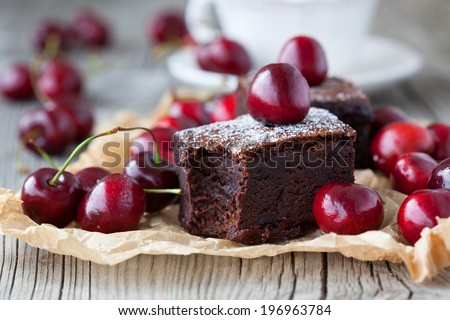 Homemade brownies with fresh berry and cup of tea on old wooden background, selective focus - stock photo
