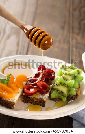 Homemade Bruschetta with fresh fruit - apricots, cherries, kiwi, salted feta cheese and honey on a rustic wooden background, selective focus - stock photo