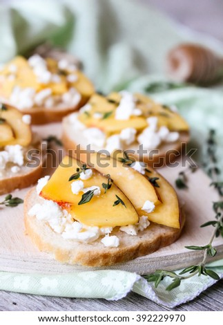 Homemade Bruschetta with nectarines, salted feta cheese, dried thyme and honey on a wooden board, selective focus - stock photo