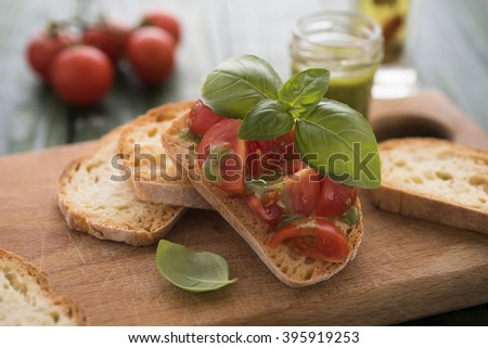 Homemade bruschetti with basil pesto and fresh tomatoes
