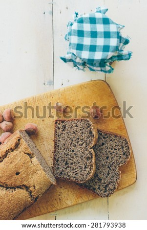 Homemade buckwheat bread on a rustic wooden table. Retro styled imagery. Grain added - stock photo