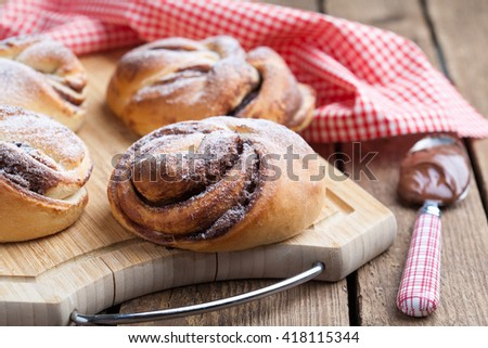 Homemade buns with chocolate and powdered sugar on the wooden table. Selective focus, dark photo. - stock photo