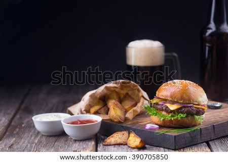 Homemade burger with beef patty, lettuce, tomato, cheese, pickled cucumbers and red onion served on wooden cutting board with fried potatoes, white sauce, ketchup and stout (dark beer) - stock photo