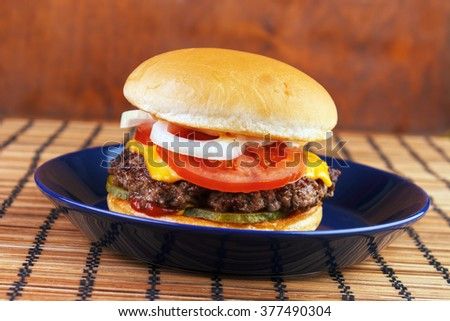 Homemade burger with cheese on blue dish - stock photo