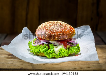 homemade burger with lettuce tomato meat ketchup mayonnaise and red onion on a wood plate and wood as background - stock photo