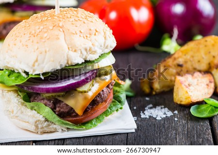 homemade burger with potato wedges on wooden table