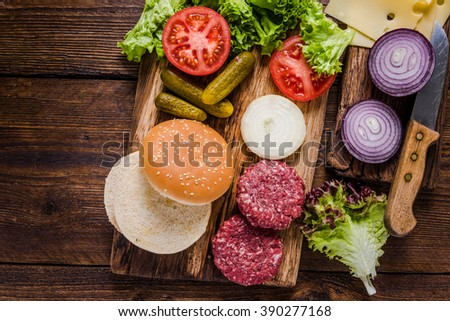 Homemade burgers ingredients on wooden rustic table - stock photo