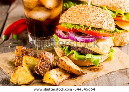 homemade burgers with beef and fried potatoes and glass of cold cola on wooden table