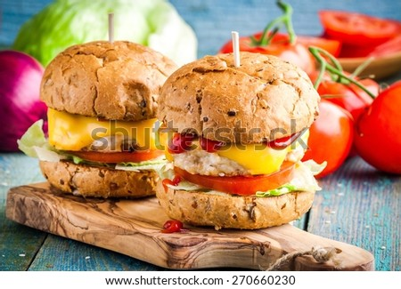 homemade burgers with fresh vegetables and chicken cutlets on wooden table - stock photo