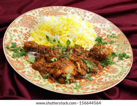 Homemade butter chicken masala with yellow and white rice, garnished with chopped coriander leaves. - stock photo