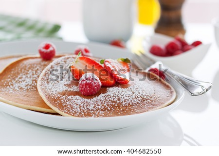 Homemade buttermilk american pancakes with fresh strawberry and raspberry on a white plate on a white table for breakfast, closeup - stock photo