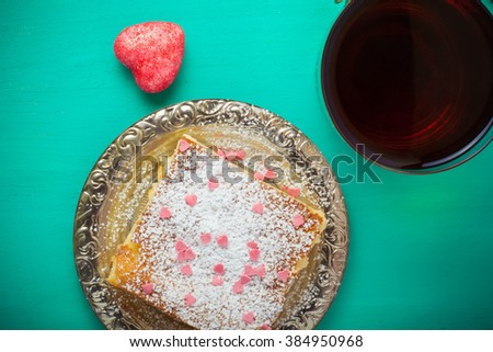 Homemade cake on a metal plate on colored wooden background. Toned.
