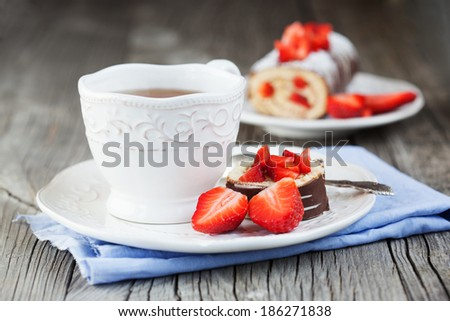Homemade cake roll with strawberry cream and a cup of tea on a wooden background, selective focus - stock photo