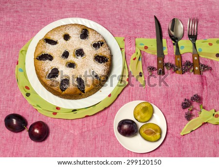 Homemade cake with plums on a pink tablecloth. Still life with cutlery, rustic style. Near knife, fork and fresh fruit. Overhead view - stock photo