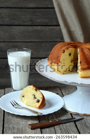 Homemade cake  with raisins and a glass of milk on a gray wooden table - stock photo