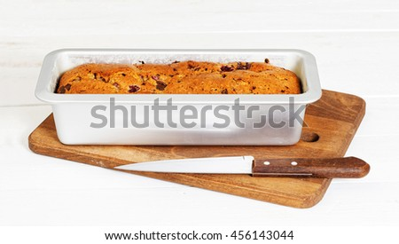 Homemade cake with raspberry and chocolate in a rectangular metal mold for baking on white wooden table - stock photo