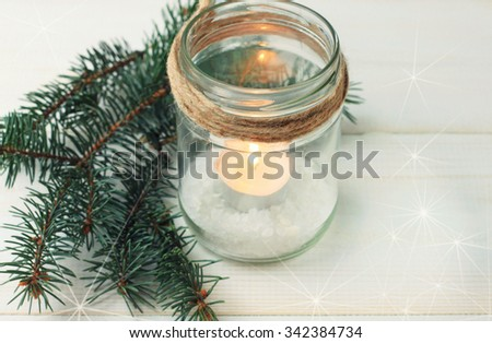 Homemade candle holder - candle in mason jar with twine and pine boughs. Soft light and focus. Toned. - stock photo