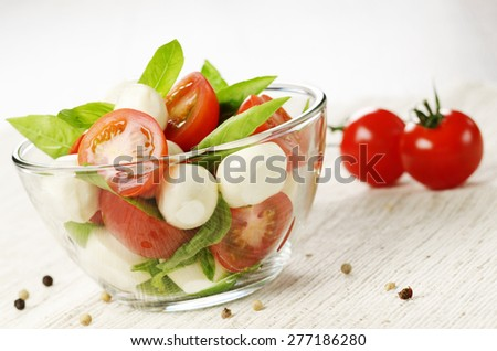 Homemade Caprese salad in glass bowl with italian bread - stock photo