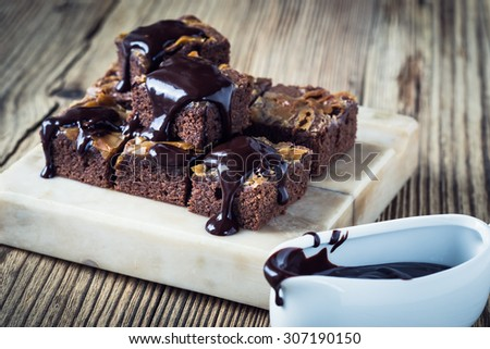 Homemade caramel chocolate brownies with dark chocolate ganache served on marble stand - stock photo
