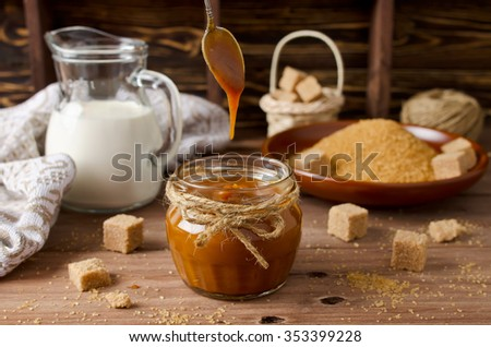 Homemade caramel sauce and ingredients on wooden table. Brown sugar, cream, butter - stock photo