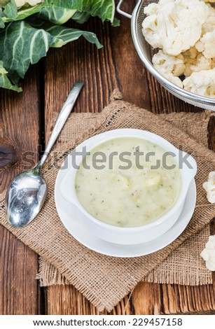 Homemade Cauliflower Soup in a bowl on wooden background - stock photo