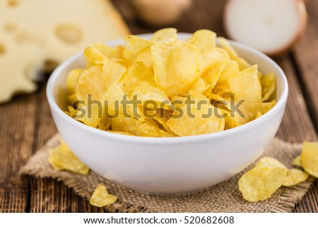 Homemade Cheese and Onion Potato Chips on vintage background (selective focus; close-up shot)