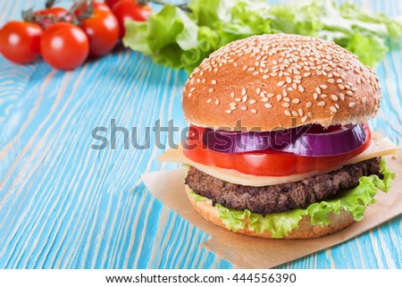 Homemade cheeseburger with beef patties and fresh salad on seasame buns, sered on blue wooden table. - stock photo