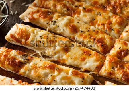 Homemade Cheesy Breadsticks with Marinara Sauce for Dipping - stock photo