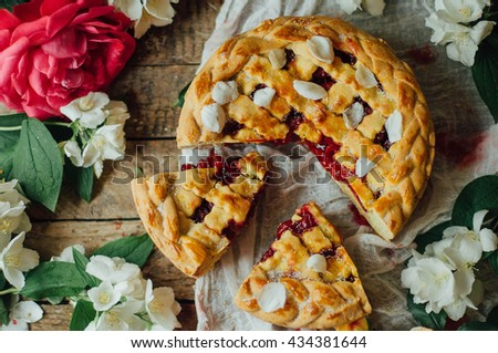 Homemade cherry and strawberry  pie on rustic background. Delicious Homemade Cherry Pie with a Flaky Crust. Rustic dark style. decorated with roses and jasmine flowers. Dessert for the family - stock photo