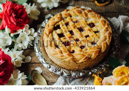 Homemade cherry and strawberry  pie on rustic background. Rustic dark style. decorated with roses and jasmine flowers. Dessert for the family - stock photo