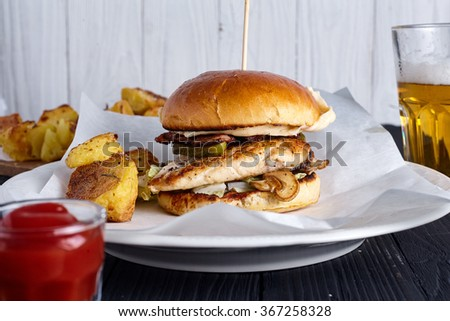 Homemade chicken burger with ketchup, beer and roasted fries potatoes on white plate on wood background. - stock photo