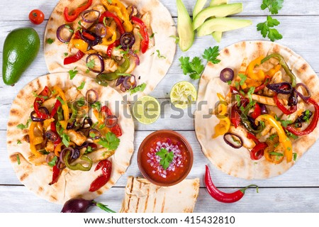 Homemade chicken Fajitas with vegetables, lime and salsa sauce on wooden background, full focus, studio lights, top view - stock photo