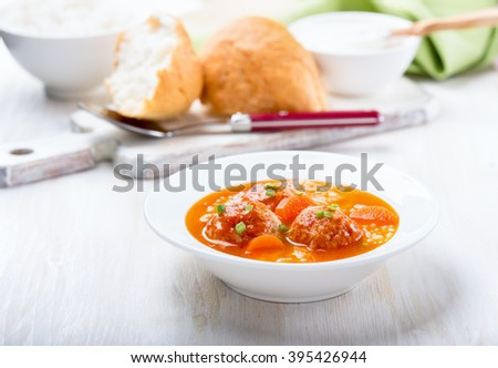 Homemade chicken meatball soup with rice in white plate, quick, hot, and delicious winter warmer meal - stock photo