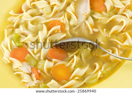 Homemade chicken noodle soup with carrots and celery in a yellow bowl, macro with copy space - stock photo