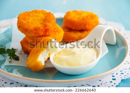 Homemade chicken nuggets with cheese sauce. - stock photo