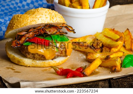 Homemade chilli burger with home spicy fries on wood board - stock photo