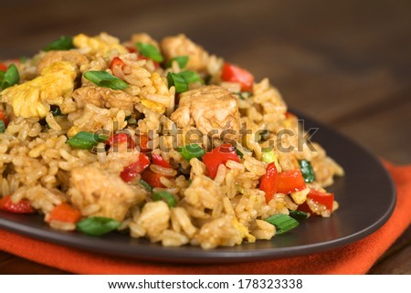 Homemade Chinese fried rice with vegetables, chicken and fried eggs served on a plate (Selective Focus, Focus one third into the dish) - stock photo