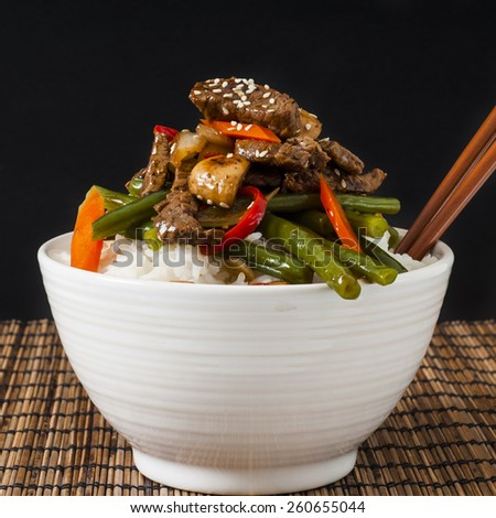 Homemade Chinese style beef and green bean stir fry on white rice - stock photo